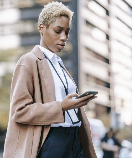 Focused black businesswoman browsing smartphone on urban street